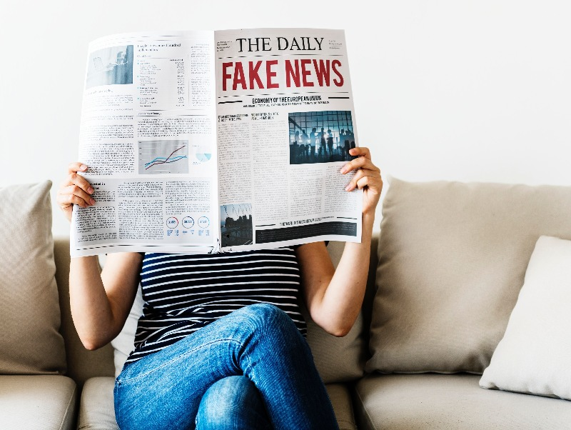 a woman reading fake news in the paper